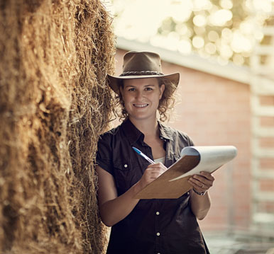 smiling woman wearing cowboy hat and holding clipboard