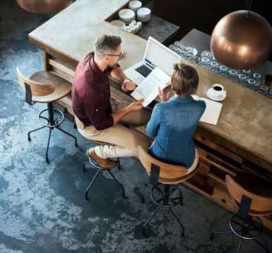 man and woman sitting at table in cafe
