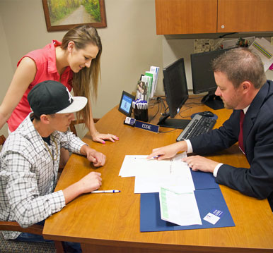 couple signing for loan with loan officer at desk