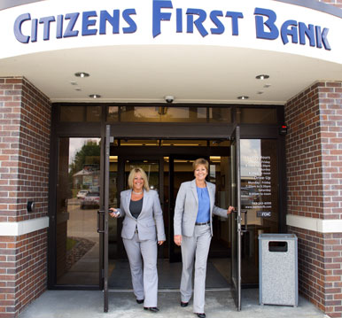 two citizens first bank employees walking out of branch building doors