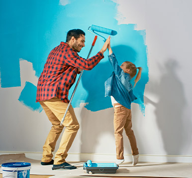 Young Father is Showing How to Paint Walls to Cute Small Daughter. They Give High Give to Each other. Rollers are Covered in Light Blue Paint.
