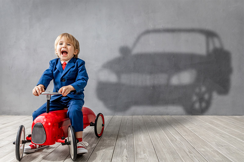 Smiling kid on a toy car projecting the shadow of a full size car