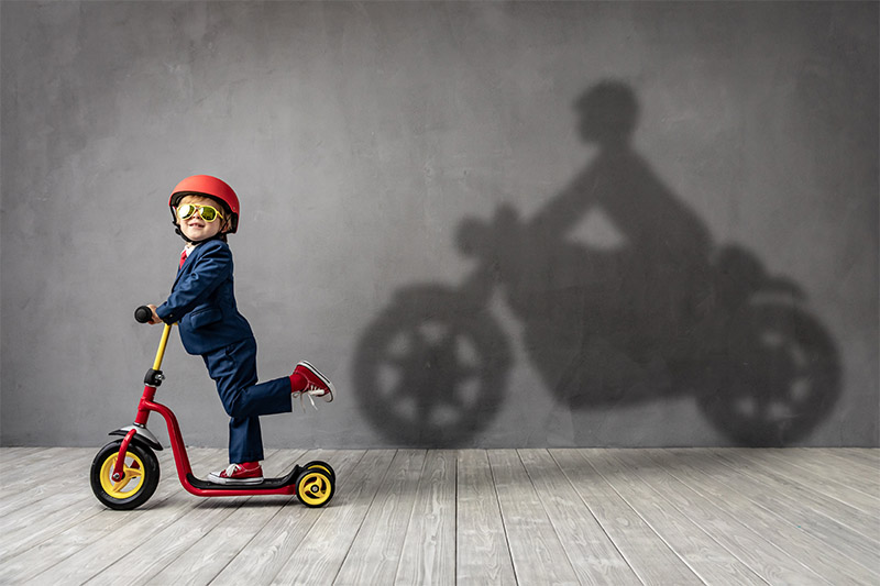 Boy on a helmet riding a small scooter projecting a motorcycle shadow