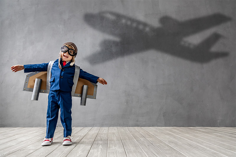Boy wearing toy airplane wings projecting an airplane shadow